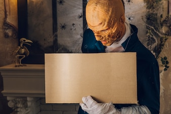 Man in Halloween mask standing with tablet