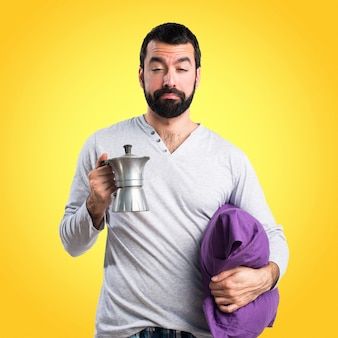 Man in pajamas holding a coffee pot on colorful background