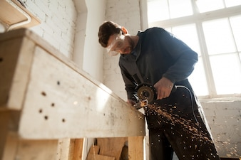 Man in protective glasses using angle grinder for cutting metal