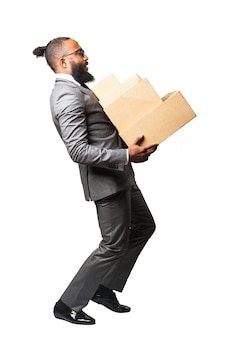 Man in suit carrying a bunch of boxes