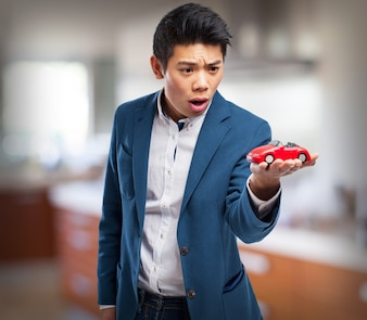 Man in suit looking surprised on a toy car