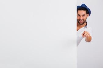 Man in summer wear behind door pointing