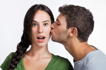 Man kissing a woman in the face