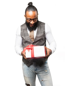 Man looking at a white gift with red bow