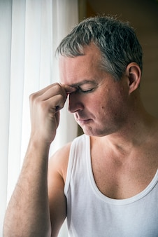 Man looking through window looking worried, depressed, thoughtful and lonely suffering depression in work pressure or personal problems concept with copy space
