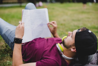 Man lying on grass reading notebook