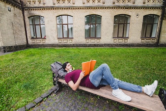 Man lying on wooden bench reading