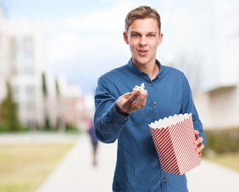 Man offering popcorn while holding a packet of popcorn