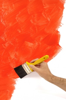 Man painting a red wall