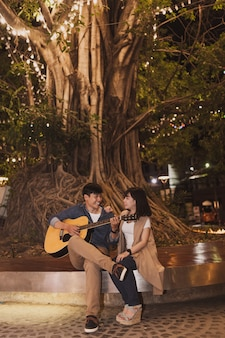 Man playing a guitar for his girlfriend under a tree