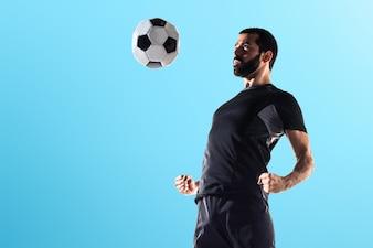 カラフルな背景でサッカーをする男