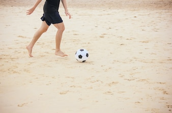 Man playing soccer ball on the beach