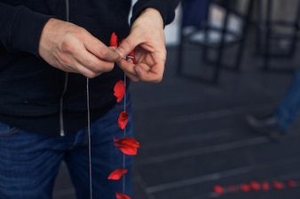 Man puts red rose petals on the thread