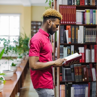 Man reading book in university library