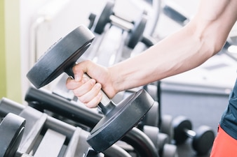 Man's hand with dumbbell