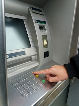 Man's using the ATM machine with cash cards and entering PIN/pass code on keypad.