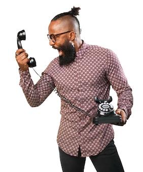 Man screaming at an old phone