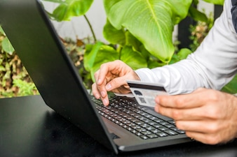 Man shopping online with his credit card from his laptop computer. Close Up Of A Man Shopping Online Using Laptop With Credit Card