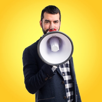 Man shouting by megaphone on colorful background