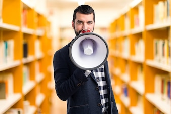 Man shouting by megaphone on unfocused background