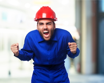 Man shouting with a blue work jumpsuit