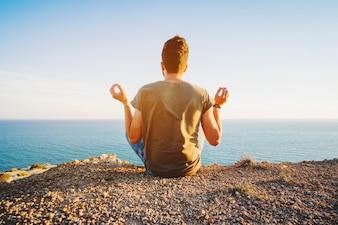 Man sitting and meditating at ocean