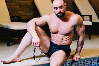 Man sitting near swimming pool