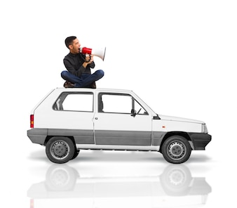 Man sitting on the roof of a car screaming for a megaphone