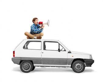 Man sitting on the roof of a car with a megaphone screaming