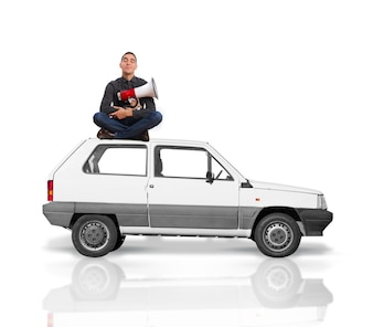 Man sitting on the roof of a car with a megaphone