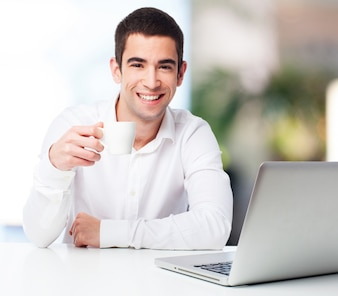 Man smiling and holding a cup of coffee