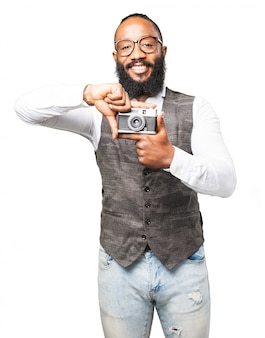 Man smiling and holding an old camera with his fingers