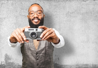 Man smiling and holding an old camera