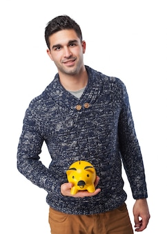 Man smiling holding a pig piggy bank