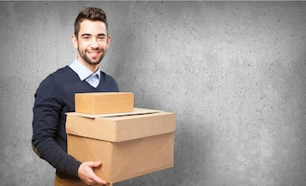 Man smiling holding cardboard boxes
