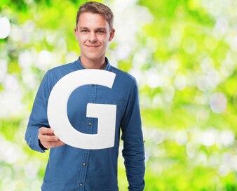 Man smiling holding the letter  g