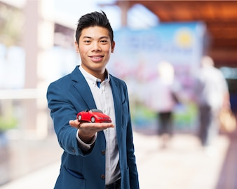 Man smiling while holding a red toy car