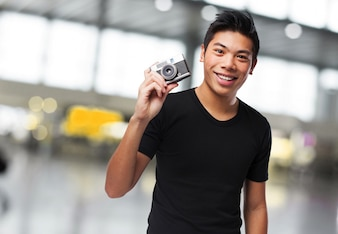 Man smiling with a camera beside his head