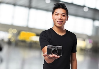 Man smiling with a photo camera on his hand