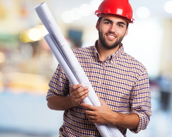 Man smiling with red helmet and blueprints