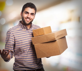 Man smiling with several cardboard boxes