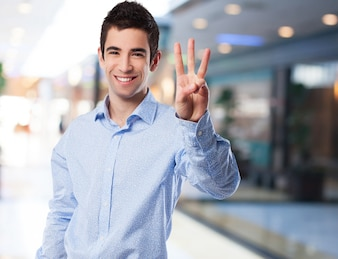 Man smiling with three raised fingers