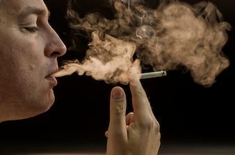 Man smoking cigarette on black background, Handsome young man smoking cigarette, Mystery man with cigar and smoke isolated on black background