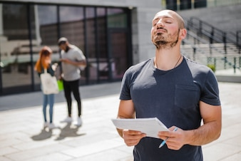 Man standing outside holding notepad meditating