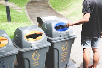 リサイクルゴミ箱にペットボトルを投げている男