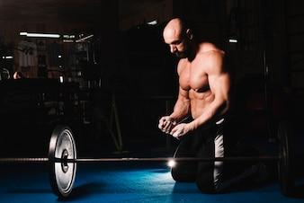 Man training with bar at gym