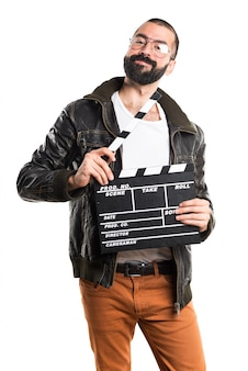 Man wearing a leather jacket holding a clapperboard