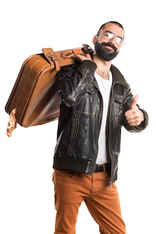 Man wearing a leather jacket holding a suitcase