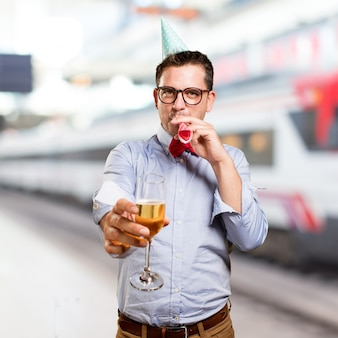 Man wearing a red bow tie and party hat. Holding a champagne gla
