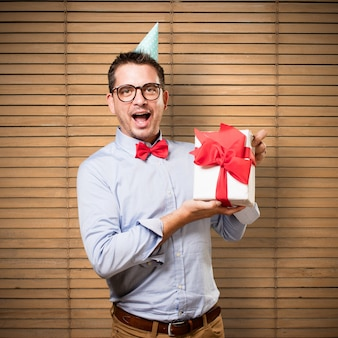Man wearing a red bow tie and party hat. Holding gift. Looking h